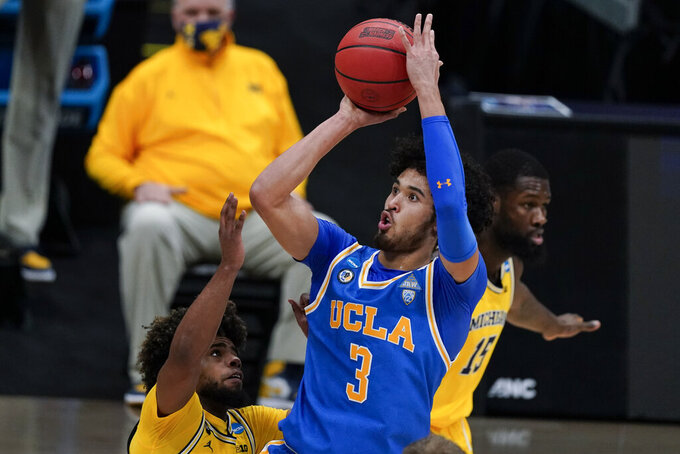 UCLA guard Johnny Juzang (3) shoots over Michigan guard Mike Smith, left, during the first half of an Elite 8 game in the NCAA men's college basketball tournament at Lucas Oil Stadium, Tuesday, March 30, 2021, in Indianapolis. (AP Photo/Michael Conroy)