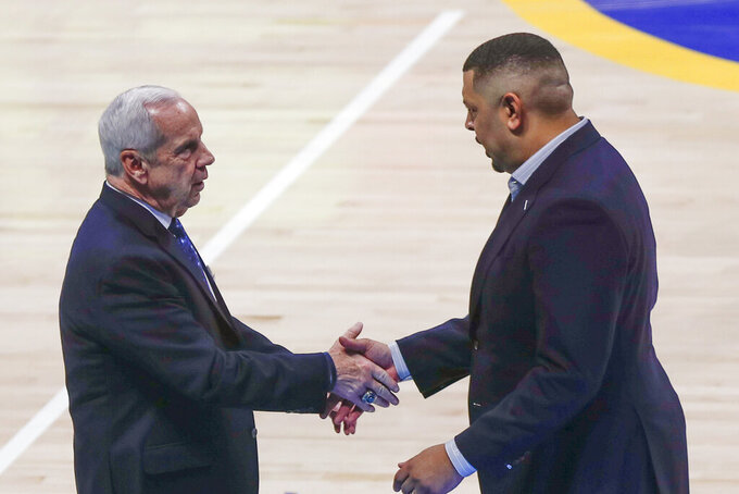 Pittsburgh head coach Jeff Capel, right, shakes hands with North Carolina head coach Roy Williams after an NCAA college basketball game, Saturday, Jan. 18, 2020, in Pittsburgh. Pittsburgh won 66-52. (AP Photo/Keith Srakocic)