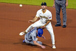 Pittsburgh Pirates second baseman Adam Frazier, top, makes the throw to first as he steps over Los Angeles Dodgers' Walker Buehler, after getting the force at second, to complete a double play on Mookie Betts during the seventh inning of a baseball game in Pittsburgh, Tuesday, June 8, 2021. (AP Photo/Gene J. Puskar)