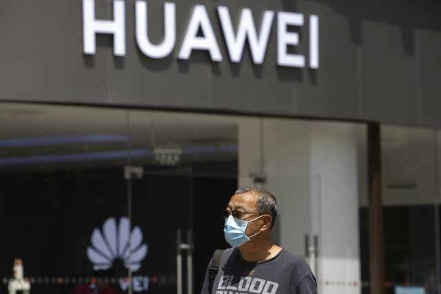 "FILE - In this May 18, 2020, file photo, a man wearing a face mask to protect against the coronavirus walks past a Huawei retail store in Beijing. One of China's biggest tech companies has criticized the Trump administration for ""politicizing business"" after it slapped export sanctions on 33 more Chinese enterprises and government entities. The announcement expanded a U.S. campaign against Chinese companies Washington says might be security threats or involved in human rights abuses. Beijing criticized curbs imposed earlier on tech giant Huawei and other Chinese companies but has yet to say whether it will retaliate. (AP Photo/Ng Han Guan, File)"