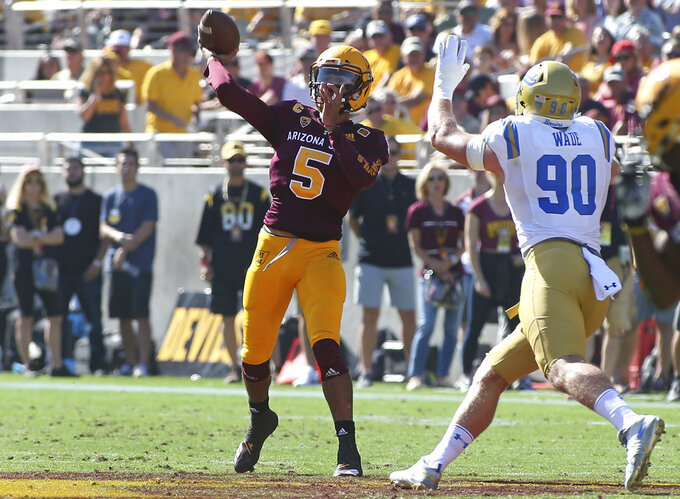 Arizona State quarterback Manny Wilkins (5) throws a pass while pressured by UCLA defensive end Rick Wade during the first half of an NCAA college football game, Saturday, Nov. 10, 2018, in Tempe, Ariz. (AP Photo/Ralph Freso)
