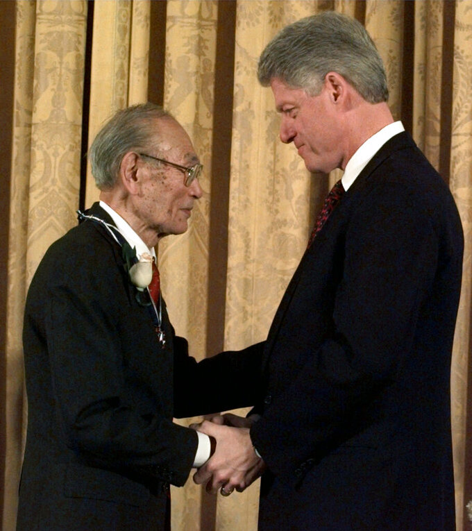 "FILE - In this Jan. 15, 1998 file photo, then President Clinton presents Fred Korematsu with a Presidential Medal of Freedom during a ceremony at the White House. Arizona is honoring late civil rights icon Korematsu, whose fight against Japanese American internment went all the way to the U.S. Supreme Court. Gov. Doug Ducey on Thursday, April 15, 2021, signed legislation establishing a ""Fred Korematsu Day of Civil Liberties and the Constitution"" on Jan. 30, Korematsu's birthday. The legislation comes as the nation continues to see a rise in anti-Asian crimes that started with the pandemic. (AP Photo/Dennis Cook, File)"