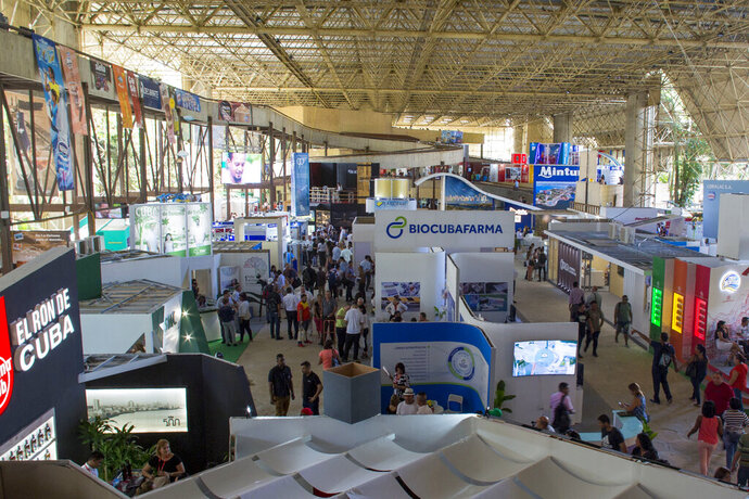 People attend the Havana International Trade Fair, in Havana, Cuba, Wednesday, Nov. 6, 2019. The trade fair is where Cuba puts the best face on of its struggling economy. (AP Photo/Ismael Francisco)