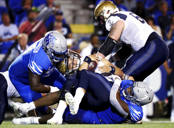 Navy quarterback Tai Lavatai (1) gets sacked during the team's NCAA college football game against Memphis on Thursday, Oct. 14, 2021, in Memphis, Tenn. (Patrick Lantrip/Daily Memphian via AP)