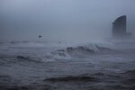 A seagull flies amid a storm in Barcelona's beach, Spain, Wednesday, Jan. 22, 2020. Massive waves and gale-force winds smashed into seafront towns, damaging many shops and restaurants and flooding some streets. (AP Photo/Joan Mateu)