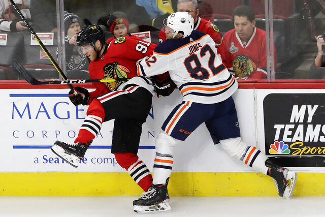 Chicago Blackhawks center Drake Caggiula, left, is checked by Edmonton Oilers defenseman Caleb Jones during the first period of an NHL hockey game in Chicago, Thursday, March 5, 2020. (AP Photo/Nam Y. Huh)