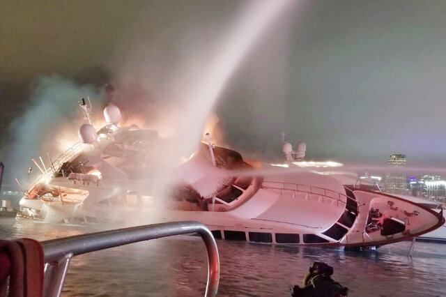 In this Dec. 18, 2019 photo made available by the Miami-Dade Fire Rescue, shows a yacht belonging to singer Marc Anthony in flames at a dock in Miami. The luxury yacht partially sank in Biscayne Bay after 45 firefighters took two hours to extinguish the blaze. (Miami-Dade Fire Rescue via AP)