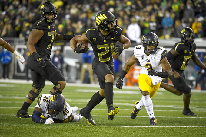 Oregon running back Byron Cardwell (21) runs past California linebacker Marqez Bimage (46) and California safety Elijah Hicks (3) during the fourth quarter of an NCAA college football game Friday, Oct. 15, 2021, in Eugene, Ore. (AP Photo/Andy Nelson)