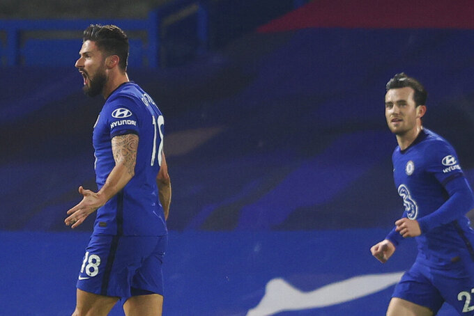 Chelsea's Ben Chilwell, right, runs to celebrate with Olivier Giroud, left, who scored his side's first goal during the English Premier League soccer match between Chelsea and Aston Villa in London, England, Monday, Dec. 28, 2020. (Richard Heathcote/Pool via AP)