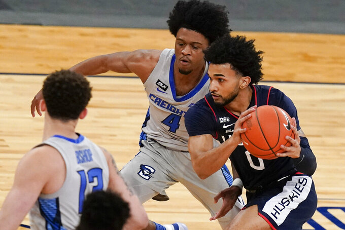 Connecticut's Jalen Gaffney (0) drives past Creighton's Shereef Mitchell (4) during the first half of an NCAA college basketball game in the semifinals in the Big East men's tournament Friday, March 12, 2021, in New York. (AP Photo/Frank Franklin II)