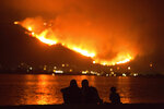 A family sits along the shore of Lake Elsinore as they watch the Holy Fire burn in the distance on Thursday night, Aug. 9, 2018 in Lake Elsinore, Calif.  More than a thousand firefighters battled to keep a raging Southern California forest fire from reaching foothill neighborhoods Friday before the expected return of blustery winds that drove the flames to new ferocity a day earlier. (AP Photo/Patrick Record)