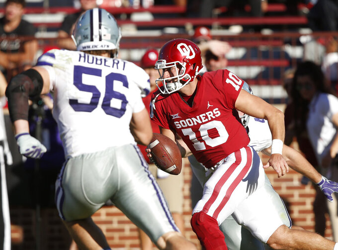 Oklahoma quarterback Austin Kendall (10) carries past Kansas State defensive end Wyatt Hubert (56) in the second half of an NCAA college football game in Norman, Okla., Saturday, Oct. 27, 2018. (AP Photo/Sue Ogrocki)