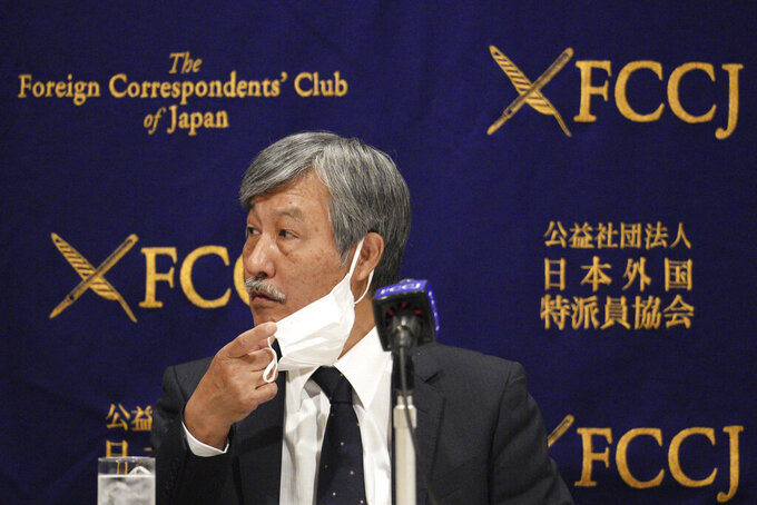 Dr. Naoto Ueyama, chairman of Japan Doctors Union, takes off his face mask during a press conference Thursday, May 27, 2021, in Tokyo. Dr. Ueyama warned Thursday that holding the one-year-delayed Tokyo Olympics in two months could lead to the spread of mutant variants of the coronavirus. (AP Photo/Eugene Hoshiko)