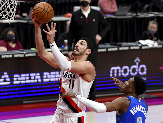 Portland Trail Blazers center Enes Kanter, left, drives to the basket on Dallas Mavericks guard Josh Richardson during the first half of an NBA basketball game in Portland, Ore., Friday, March 19, 2021. AP Photo/Steve Dykes)