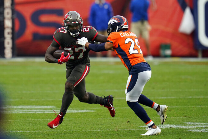 Tampa Bay Buccaneers running back Ronald Jones runs with the ball as Denver Broncos cornerback Bryce Callahan defends during the second half of an NFL football game Sunday, Sept. 27, 2020, in Denver. (AP Photo/David Zalubowski)
