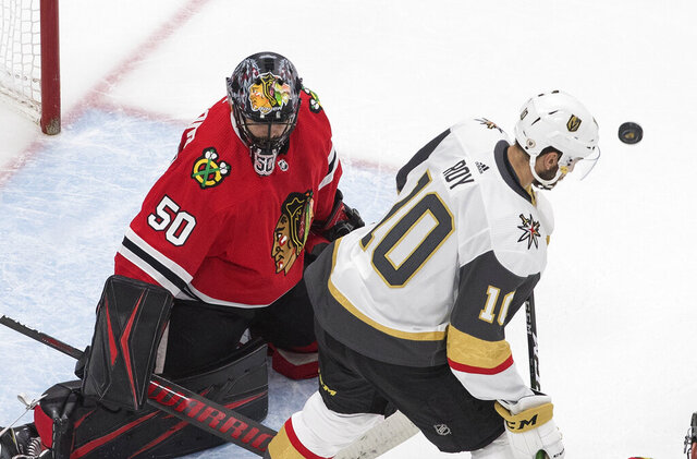 Vegas Golden Knights' Nicolas Roy (10) looks for the rebound off Chicago Blackhawks goalie Corey Crawford (50) during the third period in Game 4 of an NHL hockey first-round playoff series Sunday, Aug. 16, 2020, in Edmonton, Alberta. (Jason Franson/The Canadian Press via AP)