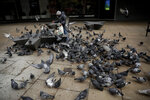 A woman feeds mostly pigeons just off Oxford Street in London, Friday, Jan. 15, 2021, during England's third national lockdown since the coronavirus outbreak began. The U.K. is under an indefinite national lockdown to curb the spread of the new variant, with nonessential shops, gyms and hairdressers closed, most people working from home and schools largely offering remote learning. (AP Photo/Matt Dunham)