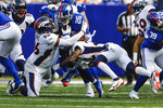 New York Giants running back Saquon Barkley (26) is tackled by Denver Broncos' Shelby Harris (96) and Kareem Jackson (22) during the first half of an NFL football game Sunday, Sept. 12, 2021, in East Rutherford, N.J. (AP Photo/Adam Hunger)
