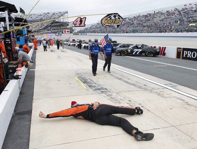 Ray Gallahan, jack man for Corey Lajoie, stretches on pit road before the NASCAR Cup Series playoff auto race, Sunday, Oct. 6, 2019, at Dover International Speedway in Dover, Del. (AP Photo/Jason Minto)