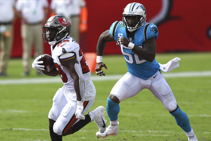 Tampa Bay Buccaneers running back Leonard Fournette (28) outruns Carolina Panthers outside linebacker Tahir Whitehead (52) during the second half of an NFL football game Sunday, Sept. 20, 2020, in Tampa, Fla. (AP Photo/Jason Behnken)