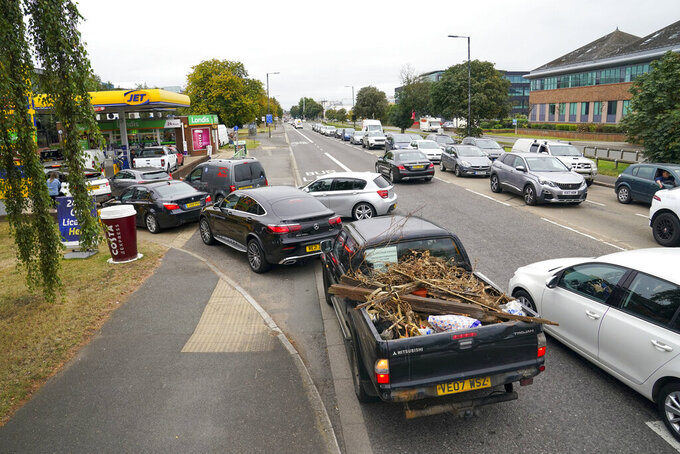 Cars queue outside a petrol station in Slough, England, Saturday Sept. 25, 2021. The haulage industry says the U.K. is short tens of thousands of truckers, due to a perfect storm of factors including the coronavirus pandemic, an aging workforce and an exodus of European Union workers following Britain's departure from the bloc. BP and Esso shut a handful of their gas stations this week, and motorists have formed long lines as they try to fill up in case of further disruption. (Steve Parsons/PA via AP)