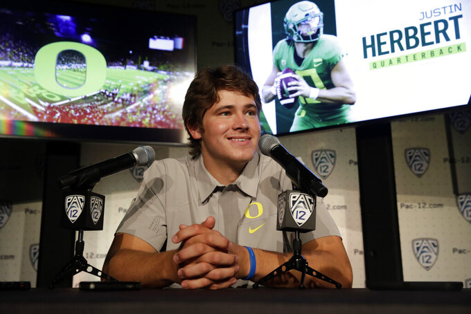 File-This July 24, 2019, file photo shows Oregon quarterback Justin Herbert answering questions during the Pac-12 Conference NCAA college football Media Day in Los Angeles. Oregon coach Mario Cristobal figures the Ducks will have 19 days of traditional fall camp before they start preparing for Auburn. Oregon's opener, a rematch of sorts of the 2011 national championship game, is set for Aug. 31 at AT&T Stadium in Arlington, Texas.(AP Photo/Marcio Jose Sanchez, File)