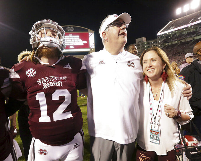 Mississippi State head coach Joe Moorhead, center, along with his wife Jen, right, and quarterback Rip Kirk (12) sing the Mississippi State alma mater after an NCAA college football game against Louisiana Tech, Saturday, Nov. 3, 2018, in Starkville, Miss. (AP Photo/Jim Lytle)