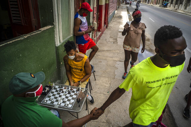 People wearing masks as a precaution against the spread of the new coronavirus walk on a street while others play chess on a sidewalk in Havana, Cuba, Wednesday, Sept. 23, 2020. The Trump administration tightened sanctions against Cuba Wednesday, prohibiting travelers from bringing rum and cigars into the U.S. and issuing an expanded list of hotels and tourist venues that Americans can no longer book for stays on the island. (AP Photo/Ramon Espinosa)