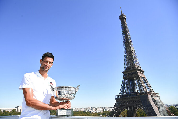 Serbia's Novak Djokovic poses with the trophy in front of the Eiffel tower during a photocall, Monday, June 14, 2021 in Paris, one day after winning French Open tennis tournament against Stefanos Tsitsipas of Greece. (Christophe Archanbault, Pool via AP)