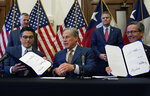 With the help of state Rep. Chris Paddie, left, and state Sen. Kelly Hancock, right, Texas Gov. Greg Abbott, center, displays two energy related bills he signed, Tuesday, June 8, 2021, in Austin, Texas. Abbot signed legislation into law to reform the Electric Reliability Council of Texas (ERCOT) and weatherize and improve the reliability of the state's power grid. (AP Photo/Eric Gay)