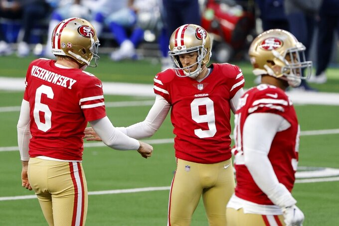 San Francisco 49ers' Mitch Wishnowsky (6) and Robbie Gould (9) celebrate a field goal kicked by Wishnowsky in the second half of an NFL football game against the Dallas Cowboys in Arlington, Texas, Sunday, Dec. 20, 2020. (AP Photo/Michael Ainsworth)