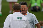 Justin Rose, of England, is congratulated by his caddie David Clark on the 18th green after their first round of the Masters golf tournament on Thursday, April 8, 2021, in Augusta, Ga. (AP Photo/Matt Slocum)