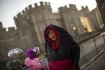 A woman who spent the night outside Windsor Castle in Windsor, England, stands inside her sleeping bag, early Thursday, May 17, 2018, ahead of Prince Harry and Meghan Markle's wedding. Preparations continue in Windsor ahead of the royal wedding of Britain's Prince Harry and Meghan Markle on Saturday May 19. (AP Photo/Emilio Morenatti)