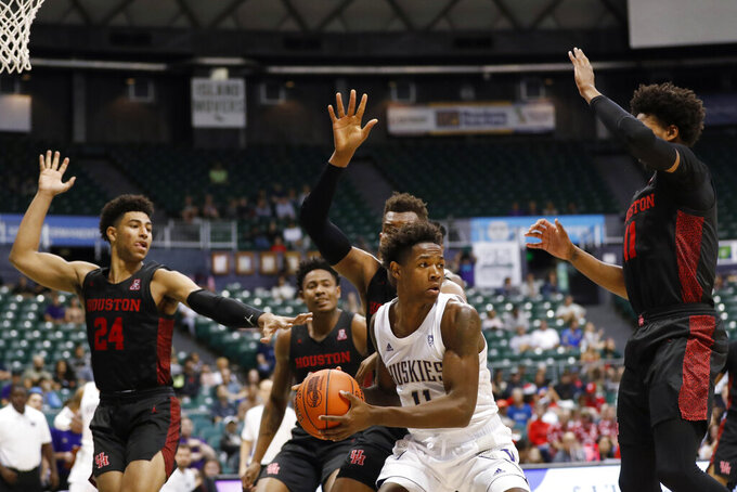 Washington guard Nahziah Carter (11) looks to get around around the Houston defense during the second half of an NCAA college basketball game Wednesday, Dec. 25, 2019, in Honolulu. (AP Photo/Marco Garcia)