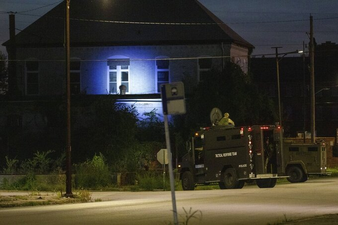 Illinois State Police in armored trucks shine a spotlight on a building near St. Louis Avenue and Sixth Street in East St. Louis, Ill. during a manhunt after a shooting on Thursday, Sept. 9, 2021. Multiple victims were reported shot in southern Illinois late Thursday afternoon and  at least three suspects who crashed their getaway vehicle into a passenger train remained on the loose, authorities said. (Daniel Shular/St. Louis Post-Dispatch via AP)