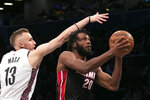 Brooklyn Nets guard Dzanan Musa (13) tries to block a shot by Miami Heat forward Justise Winslow (20) in the first half of an NBA basketball game, Sunday, Dec. 1, 2019 in New York. (AP Photo/Mark Lennihan)