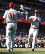 Philadelphia Phillies' Scott Kingery, right, is congratulated by J.T. Realmuto (10) after scoring against the San Francisco Giants in the third inning of a baseball game Sunday, Aug. 11, 2019, in San Francisco. (AP Photo/Ben Margot)