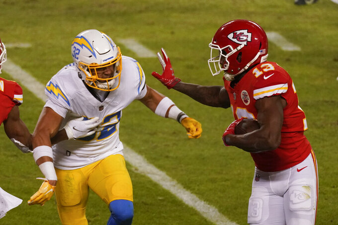 Kansas City Chiefs wide receiver Byron Pringle (13) runs from Los Angeles Chargers safety Alohi Gilman (32) after catching a pass during the second half of an NFL football game, Sunday, Jan. 3, 2021, in Kansas City. (AP Photo/Charlie Riedel)