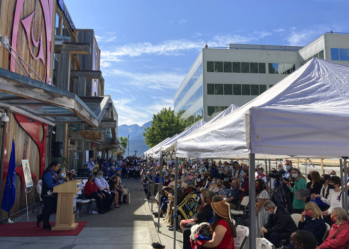 People gather for a ceremony that marked the release of the Raven Story stamp Friday, July 30, 2021 in downtown Juneau, Alaska. The stamp, issued by the U.S. Postal Service, was created by Alaska Native artist Rico Worl. (AP Photo/Becky Bohrer)