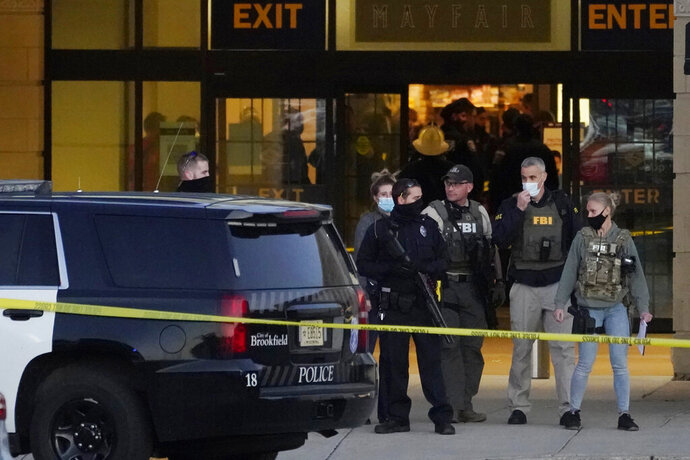 FBI officials and police stand outside the Mayfair Mall after a shooting, Friday, Nov. 20, 2020, in Wauwatosa, Wis. Multiple people were shot Friday afternoon at the mall. Wauwatosa Mayor Dennis McBride says in a statement that a suspect remains at large after the shooting at Mayfair Mall.  (AP Photo/Nam Y. Huh)