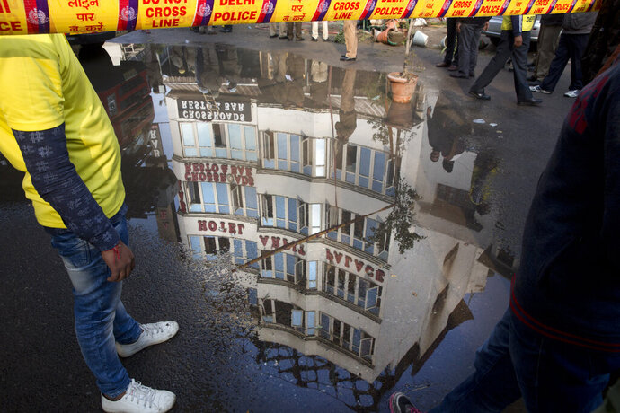 The Arpit Palace Hotel is reflected in a puddle after an early morning fire at the hotel killed more than a dozen people in the Karol Bagh neighborhood of New Delhi, India, Tuesday, Feb.12, 2019. (AP Photo/Manish Swarup)
