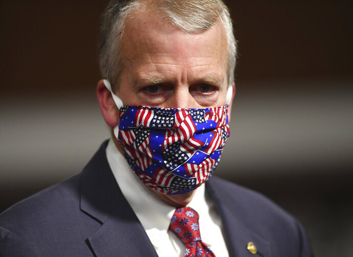 FILE - In this May 7, 2020, file photo, Sen, Dan Sullivan, R-Ark., wears a mask at a hearing in Washington. Protesters in Alaska carrying a banner and a caribou heart interrupted a campaign event for Sullivan who is seeking reelection. The Anchorage Daily News reported the small group of protesters were restrained and escorted out by staff and attendees at Sullivan's campaign launch event in a hangar near Ted Stevens Anchorage International Airport, Saturday, July 11. (Kevin Dietsch/Pool via AP, File)