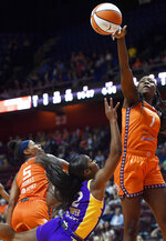 Connecticut Sun center Beatrice Mompremier (1) blocks a shot from Los Angeles Sparks guard Te'a Cooper during a WNBA basketball game Thursday, Aug. 26, 2021, in Uncasville, Conn. (Sean D. Elliot/The Day via AP)