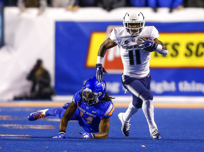 Utah State wide receiver Aaren Vaughns (11) runs past a diving Boise State cornerback Tyler Horton (14) during the first half of an NCAA college football game Saturday, Nov. 24, 2018, in Boise, Idaho. (AP Photo/Steve Conner)