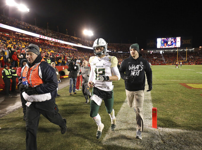 Baylor quarterback Charlie Brewer, center, is escorted off the field after he was ejected during the second half of an NCAA college football game against Iowa State, Saturday, Nov. 10, 2018, in Ames. (AP Photo/Matthew Putney)