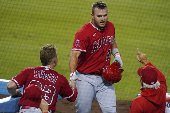 Los Angeles Angels' Mike Trout, center, returns to the dugout after hitting a three-run home run during the third inning of the team's baseball game against the Los Angeles Dodgers on Friday, Sept. 25, 2020, in Los Angeles. (AP Photo/Ashley Landis)