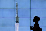 A woman wearing a face mask is silhouetted as she walks by a TV screen showing CCTV live telecast of the Long March-2F Y12 rocket carrying a crew of Chinese astronauts in a Shenzhou-12 spaceship lifts off at the Jiuquan Satellite Launch Center, at a shopping mall in Beijing, Thursday, June 17, 2021. China launched the first three crew members on a mission to its new space station Thursday in its first crewed mission in five years. (AP Photo/Andy Wong)