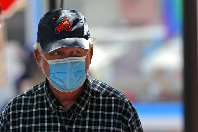 A man wears a mask to help fight the spread of the coronavirus, Thursday, July 30, 2020, in Portland, Maine.   State officials reported more cases of COVID-19. (AP Photo/Robert F. Bukaty)