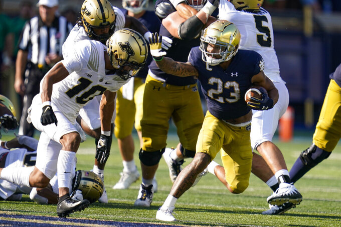 Notre Dame running back Kyren Williams (23) pushes off Purdue safety Cam Allen (10) after he picks up yardage during the second half of an NCAA college football game in South Bend, Ind., Saturday, Sept. 18, 2021. Notre Dame defeated Purdue 27-13. (AP Photo/Michael Conroy)