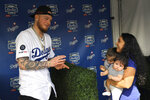Los Angeles Dodgers' Alex Verdugo, left, gets ready to have his picture taken with Desirae Cortez, right, along with her children Emma, second from left, and Julianna during Dodger Stadium FanFest Saturday, Jan. 25, 2020, in Los Angeles. (AP Photo/Mark J. Terrill)